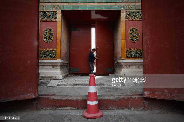 A worker closes a red door of the entrance to Jian Fu Palace inside the Forbidden City which was the Chinese imperial palace from the midMing Dynasty...