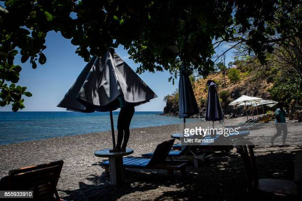 KARANGASEM BALI INDONESIA SEPTEMBER 30 A worker closes the beach umbrellas at Amed beach as emptied of tourists on September 30 2017 in Karangasem...