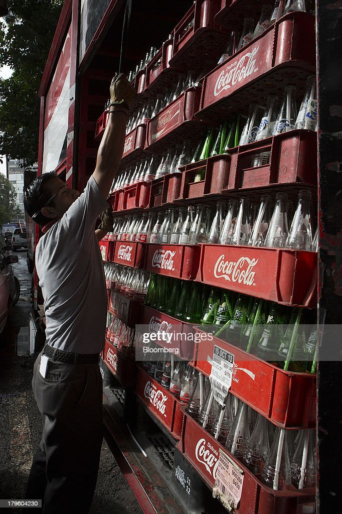 A worker closes the door of a delivery truck filled with empty Coca-Cola bottles in Mexico City, Mexico, on Thursday, Sept. 5, 2013. Coca-Cola Femsa SAB, a bottler and distributor of Coca-Cola products in Mexico, agreed to buy Brazils Spaipa SA Industria Brasileira de Bebidas in a cash deal with a total transaction value of $1.86 billion. Photographer: Susana Gonzalez/Bloomberg via Getty Images