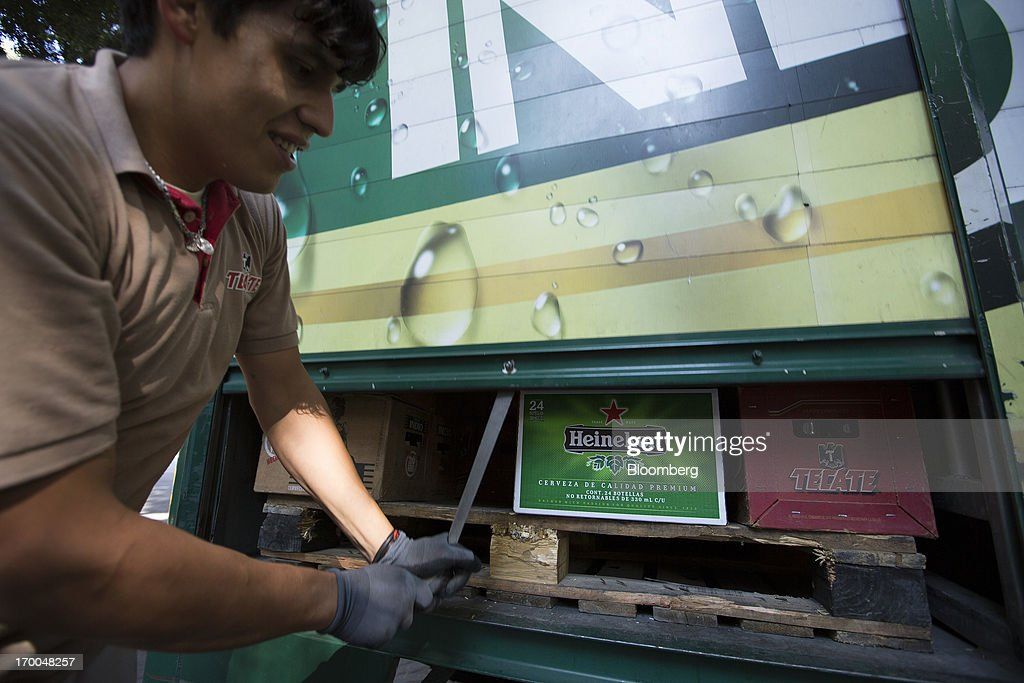 A worker closes the door of a delivery truck operated by Cuauhtemoc-Moctezuma, a subsidiary of Heineken NV, in Mexico City, Mexico, on Thursday, June 6, 2013. Heineken NV and Grupo Modelo SAB, the dominant brewers in Mexico with brands such as Dos Equis and Corona, are nearing the end of an almost three-year-old government antitrust probe. Photographer: Susana Gonzalez/Bloomberg via Getty Images