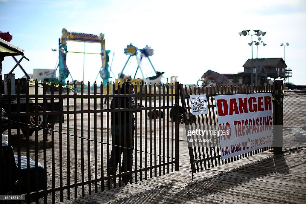A worker closes the gate of the Fun Town Pier that was damaged by Superstorm Sandy, February 19, 2013 in Seaside Heights, New Jersey. Governor Chris Christie has estimated that damage in New Jersey caused by Superstorm Sandy could reach $37 billion.