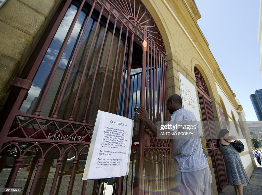 A worker closes the main entrance of the France-Brazil Cultural Centre on February 1, 2013 in Rio de Janeiro, Brazil. Ensueing the fire at the Kiss nightclub in Santa Maria that killed 236 people, Rio's government closed 49 theaters, cultural centers and local restaurants not compliant with the safety regulations.