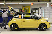 A worker closes the trunk of a finished Opel Adam car at the assembly line shortly after a celebration to mark the launch of the new Opel compact car...