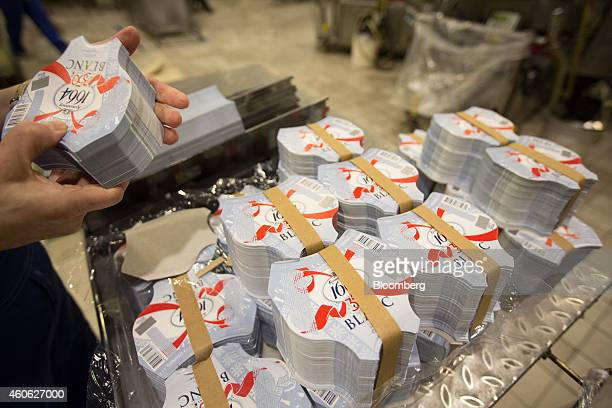 A worker collects a bundle of labels destined for bottles of Kronenbourg 1664 Blanc beer on the production line at the OAO Baltika brewery operated...