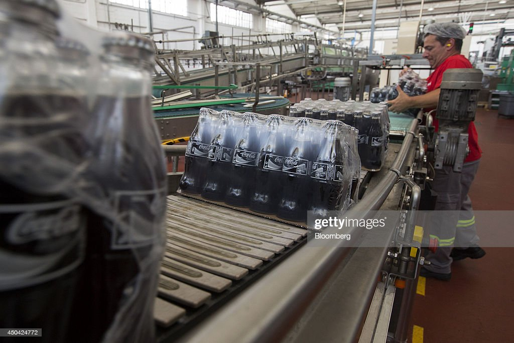 A worker collects a packaged case of Coca-Cola Light beverages, also known as diet Coke, at the end of the production line at the Lanitis Bros Ltd. bottling plant, part of the Coca-Cola Hellenic Group, in Nicosia, Cyprus, on Tuesday, June 10, 2014. Zug, Switzerland-based Coca-Cola Hellenic Bottling Co., which distributes Coca-Cola products in countries including Russia, wants to move away from using imported sugar for its Russian operations by 2015. Photographer: Andrew Caballero-Reynolds/Bloomberg via Getty Images