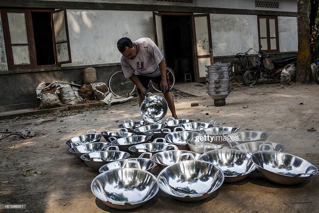 A worker collects pans that has been dried after polishing process at Putra Logam workshop on May 1, 2014 in Yogyakarta, Indonesia. The pan polishers are paid around Rp. 40.000 (USD 3.46) per day. Today is International Labour Day, which aims to bring attention to working conditions, higher wages, and working hours across the world. Protesters across Indonesia have organised rallies to demand higher wages, as Indonesia recognises its first national labour day holiday.