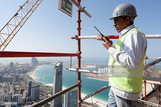 A worker communicates by radio from scaffolding above a Central Market residential tower an Aldar PJSC project under construction in Abu Dhabi United...