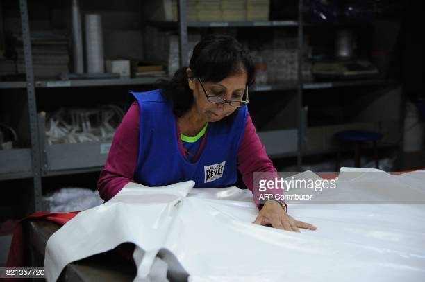 A worker completes quality control of the leather used to make boxing gloves at Reyes Industries headquarters in Mexico City on July 06 2017 Cleto...