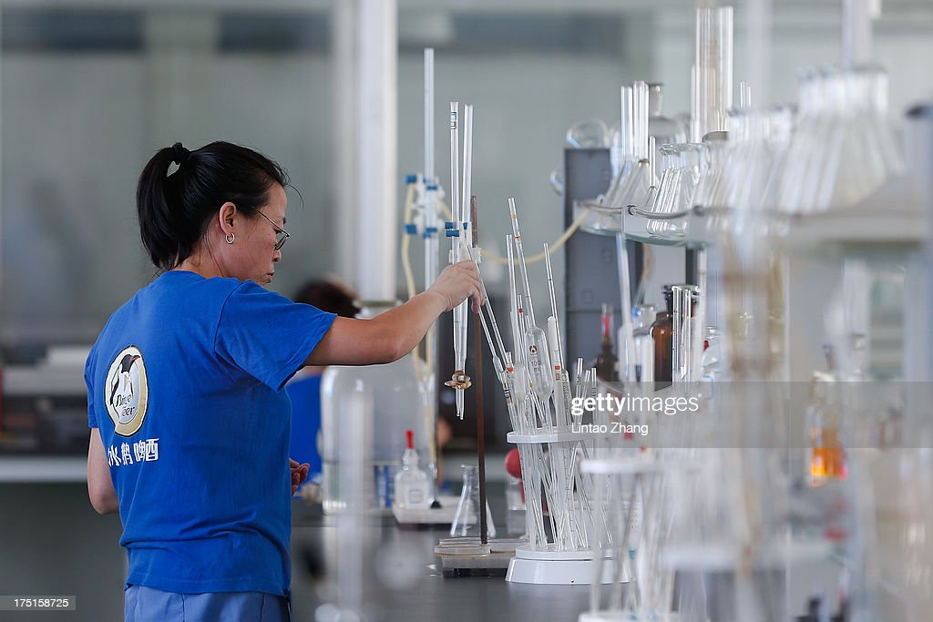 A worker conducts tests at the Jinzhu Manjiang beer factory on August 1, 2013 in Fujin, Heilongjiang Province, China. Recent significant sustained high temperatures in China are expected to push beer industry volume and revenue growth up significantly.
