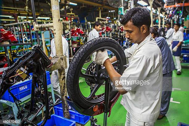 A worker connects a wheel to the forks of a Hero Ignitor motorcycle on the assembly line of the Hero MotorCorp Ltd manufacturing facility in Gurgaon...