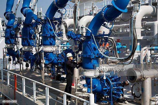 A worker connects the Tangguh Palung liquefied natural gas tanker right operated by Tangguh LNG to pipelines while it sits moored at the Korea Gas...