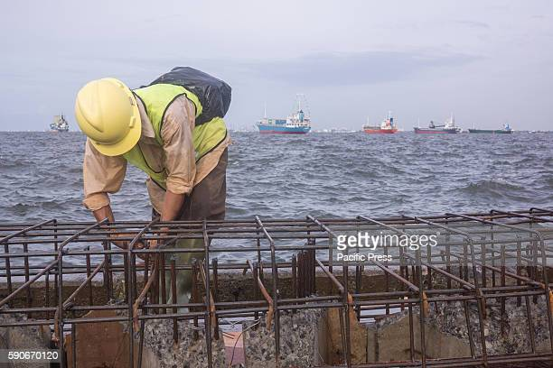 A worker constructing Jakarta's new giant sea wall Jakarta is sinking by between 75 and 17 centimetres a year more than 10 times faster than the sea...
