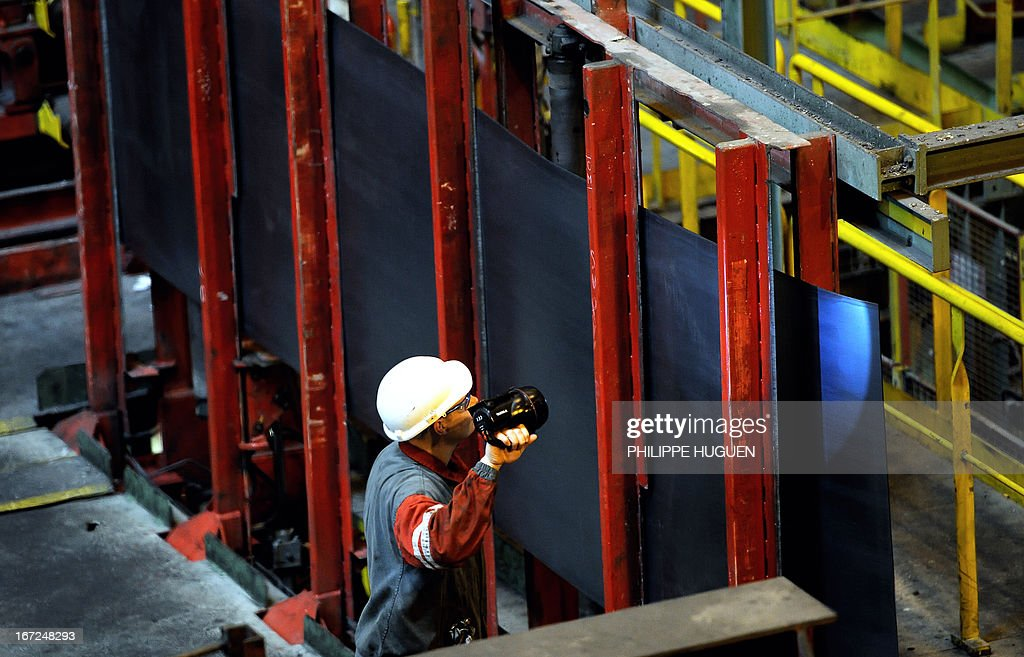 A worker controls a coil of steel at the blast furnace of the ArcelorMittal steel plant of Grande-Synthe, northern France, on April 22, 2013.