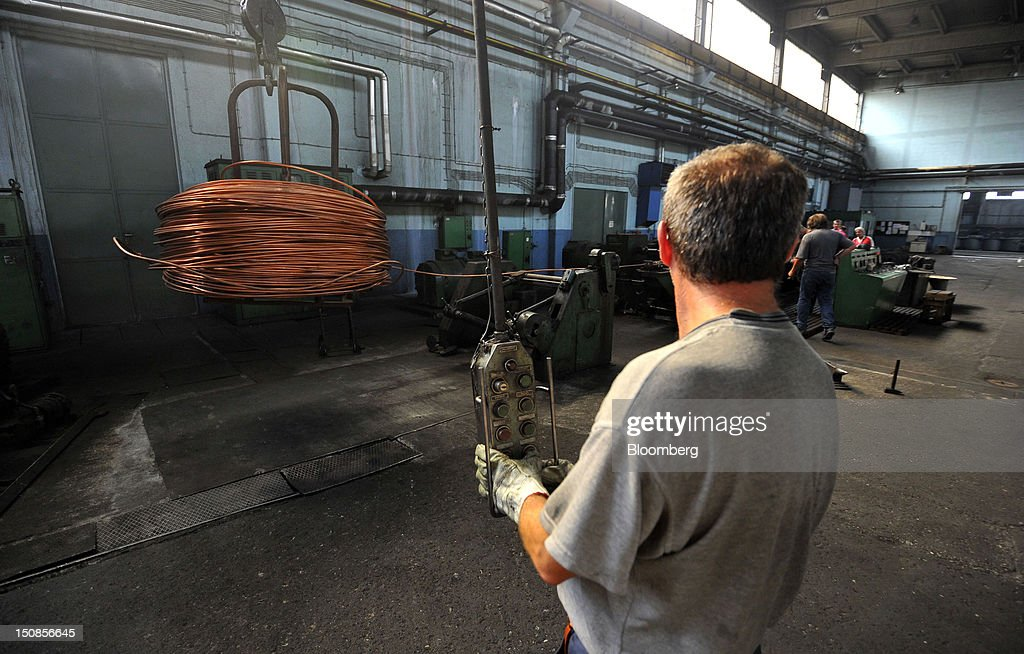 A worker controls a machine coiling lengths of copper wire at the copper mining and smelting complex, operated by RTB Bor Group, in Bor, Serbia, on Friday, Aug. 24, 2012. Copper neared a one-week low in London on signs Asian economies are slowing and speculation that U.S. policy makers will refrain from a fresh round of stimulus. Photographer: Oliver Bunic/Bloomberg via Getty Images