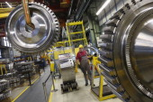 A worker controls a winch to transport a disc of a gas turbine at the Siemens gas turbine plant on November 11 2012 in Berlin Germany Earlier in the...