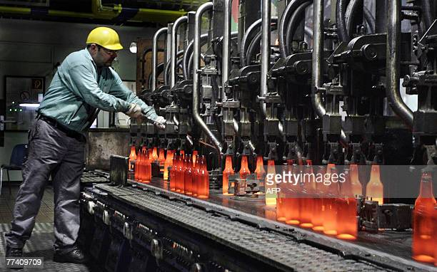 A worker controls still glowing glass bottles at the moulding machine of SaintGobain Oberland 17 October 2007 at the glass production site in Wirges...