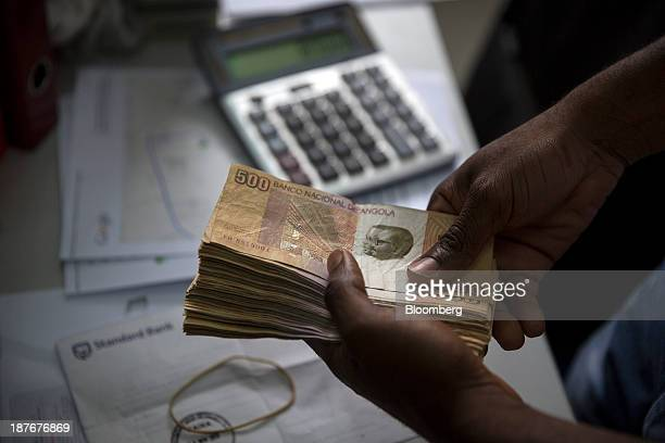 A worker counts 500 denomination kwanza currency banknotes in an office in Luanda Angola on Friday Nov 8 2013 Angola the largest crude oil producer...