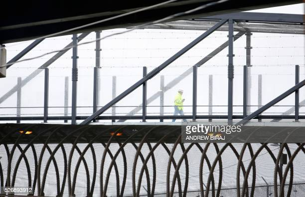 A worker crosses a bridge while inspecting cars at the scene of CSX freight train derailment near the Rhode Island Avenue metro station in Washington...