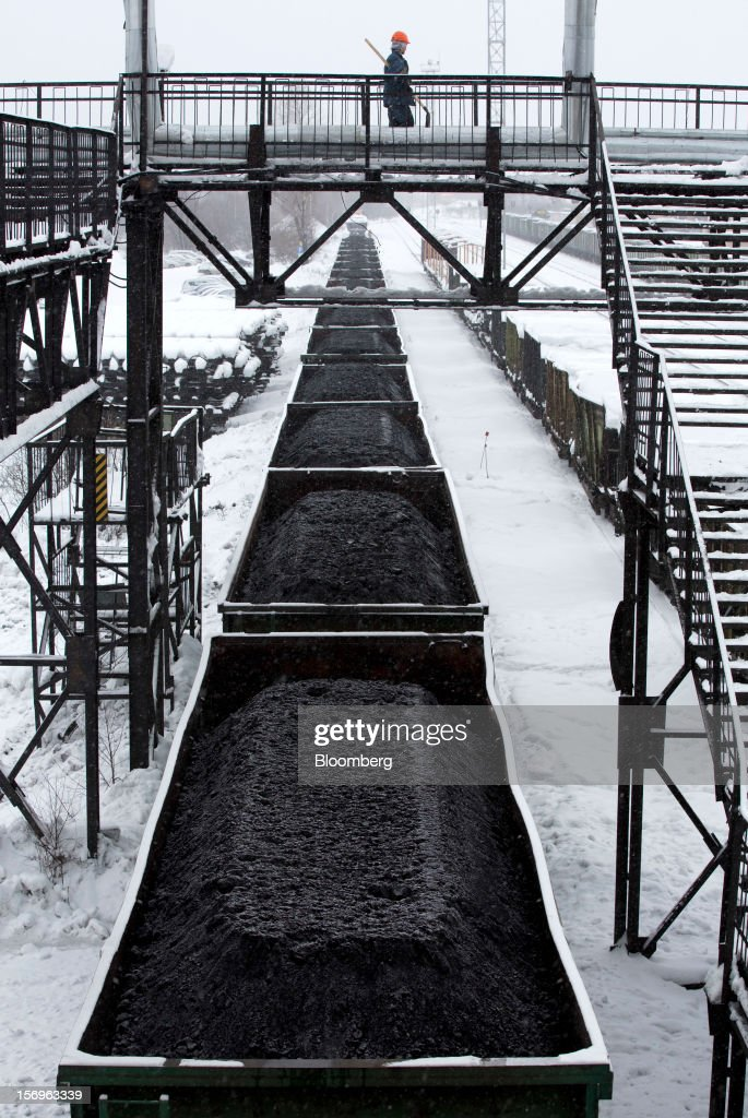 A worker crosses rail lines above freight wagons loaded with coal at the Sibirginsky open pit coal mine, owned by OAO Mechel and operated by Southern Kuzbass Coal Co., near Myski, in Kemerovo region of Siberia, Russia, on Friday, Nov. 23, 2012. OAO Mechel is Russia's biggest maker of steelmaking coal. Photographer: Andrey Rudakov/Bloomberg via Getty Images