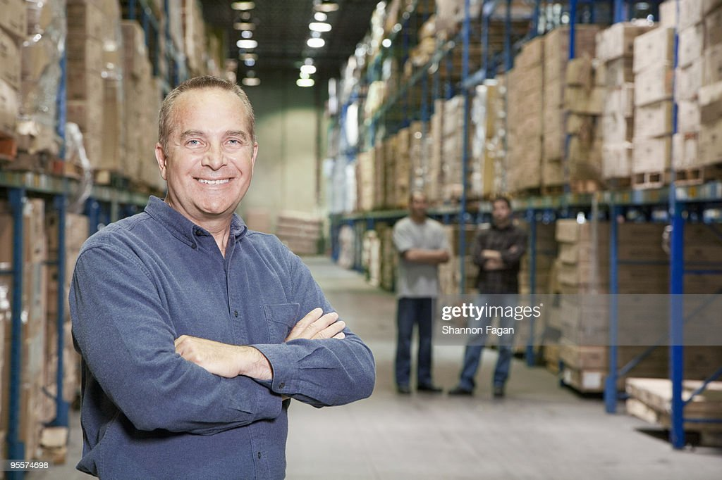 A worker crossing arms in a warehouse : Stock Photo