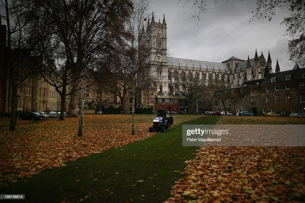 A worker cuts a green carpet through fallen Autumn leaves as he clears up in Dean's Yard in sight of Westminster Abbey on November 20, 2012 in London, England. Britain is forecasted for nationwide rains from storms stemming this week from the Atlantic.