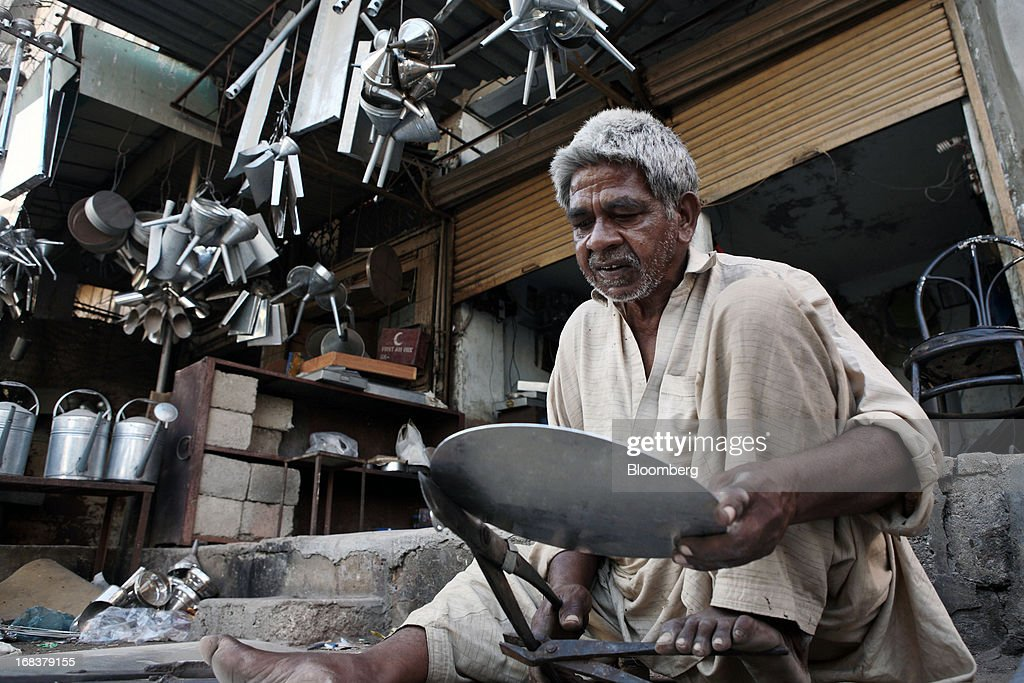 A worker cuts a steel plate using tin snips to make a small steel fryer in Karachi, Pakistan, on Wednesday, May 8, 2013. Pakistan is to hold parliamentary elections on May 11. According to opinion polls, Nawaz Sharif of the Pakistan Muslim League-N (PMLN) leads Imran Khan of Pakistan Tehrik-e-Insaf (PTI) in the race to replace president Asif Ali Zadari and become Pakistan's 12th president. Photographer: Asim Hafeez/Bloomberg via Getty Images