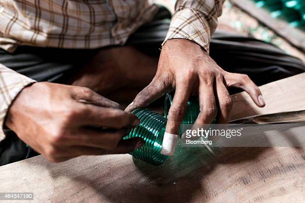 A worker cuts coils of glass with a diamond cutter into bangles at the Kohinoor Bangle Industries factory in Ferozabad Uttar Pradesh India on...