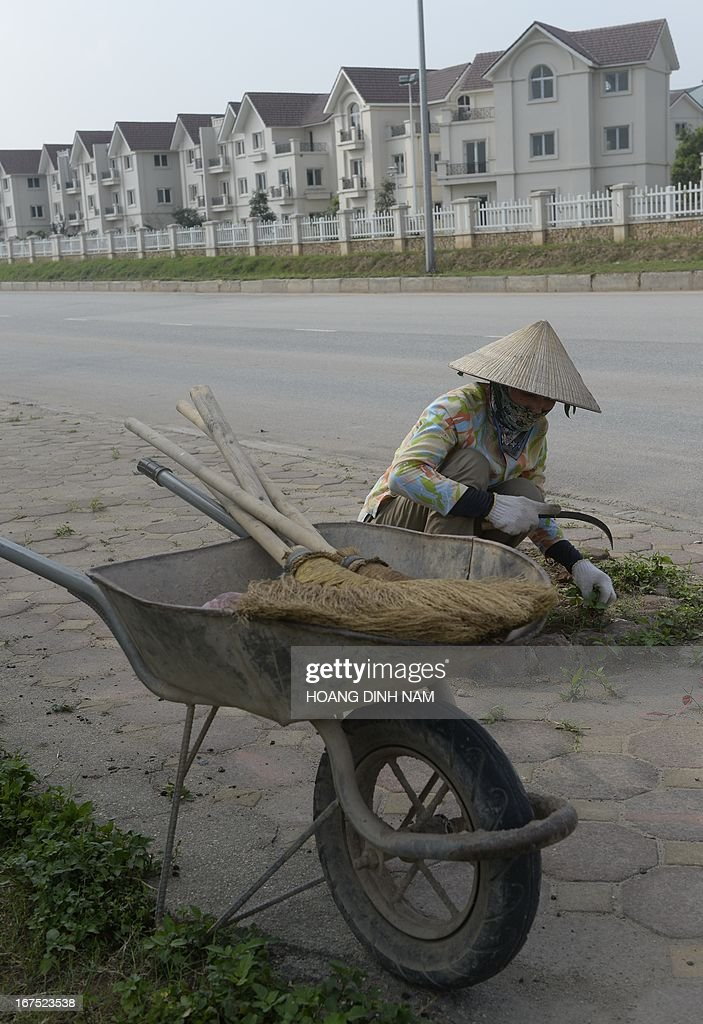 A worker cuts grass next to empty villas at a newly developed area in the suburbs of Hanoi on April 26, 2013. Toxic debts caused by a frozen property market for Vietnam's banking system is among major challenges that faces the communist nation's economy , according to the official media. AFP PHOTO/HOANG DINH Nam.