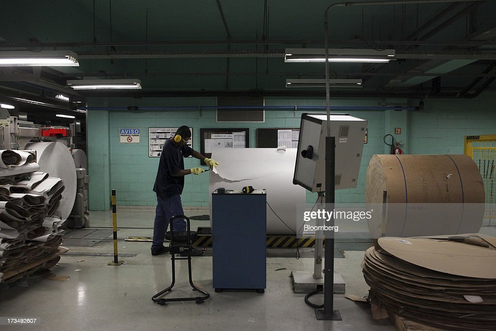 A worker cuts pieces of a damaged roll of paper before inserting it to the system at the press park of the O Globo newspaper in Rio de Janeiro, Brazil, on Friday, July 12, 2013. Brazil economists raised their 2014 benchmark interest rate forecast to the highest all year, as policy makers work to slow inflation that has curbed consumption and confidence in the world's second-biggest emerging market. Photographer: Dado Galdieri/Bloomberg via Getty Images