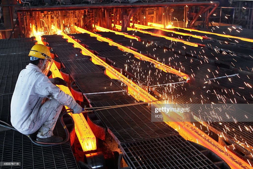 A worker cuts steel billets at an iron and steel enterprise on June 9 2014 in Ganyu County China China's consumer price index a main gauge of...