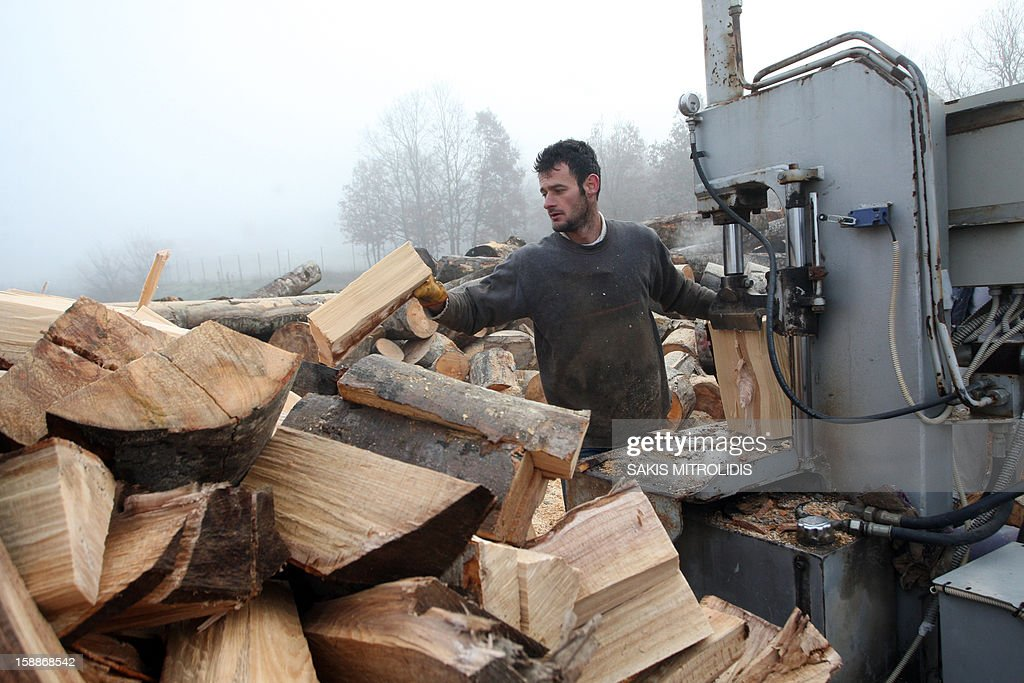 A worker cuts wood in a wood factory in Grevena, on January 2, 2013. Air pollution in cities of Greece has surged in recent days because of people choosing wood over more expensive fuels to heat their homes in the grips of a continuing economic crisis. Illegal logging has surged also in Greece as Forest Authorities reported that illegal logging activities across the country accounts for up to 30 percent of all lost forestland. AFP PHOTO /Sakis Mitrolidis