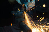 Worker cutting with grinder and welding metal with many sharp sparks in factory