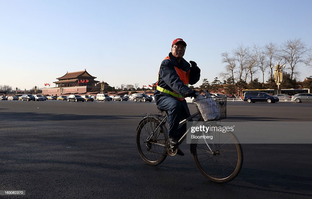 A worker cycles past Tiananmen Gate in Beijing, China, on Monday, March 4, 2013. Premier Wen Jiabao will this week formally announce this year's economic targets when he delivers his final work report to the National People's Congress, which begins on March 5. Photographer: Tomohiro Ohsumi/Bloomberg via Getty Images