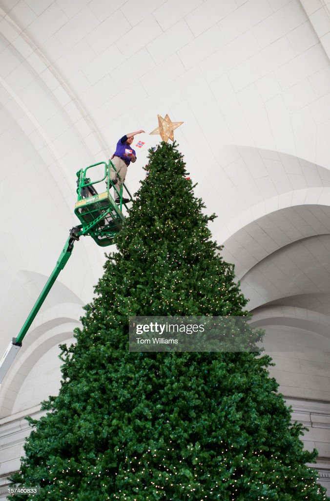 A worker decorates a Christmas tree located near the metro entrance at Union Station.