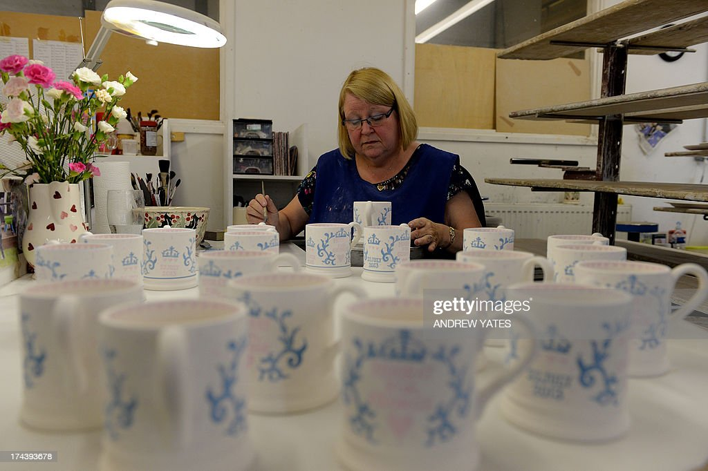 A worker decorates commemorative mugs made to mark the birth of George Alexander Louis of Cambridge to Prince William and Catherine, The Duchess of Cambridge, ahead of being kiln-fired at the Emma Bridgewater pottery in Hanley, Stoke-on-Trent on July 25, 2013 . Ever since Kate's pregnancy was announced in December, retailers have been busily producing all sorts of baby-related items, from tea towels to royal baby potties. But for many royal collectors, it is all about the hand-finished mugs and plates which they can give pride of place on a mantlepiece or a wall.