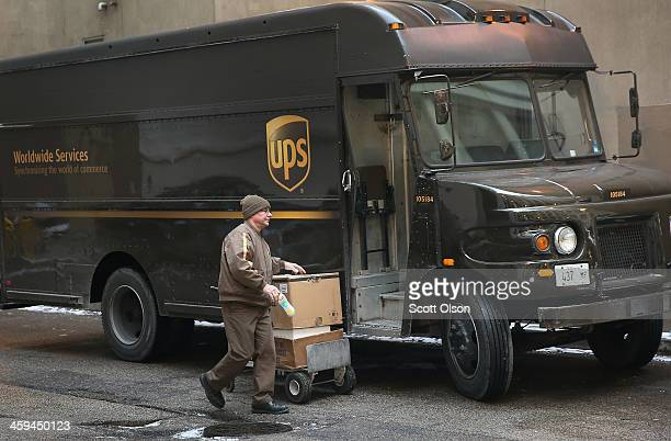 UPS worker delivers packages on December 26 2013 in Chicago Illinois Bad weather and a higher than expected demand from online sales caused FedEx and...