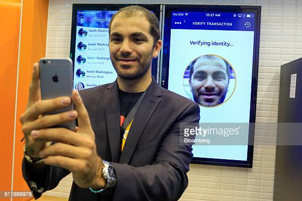 A worker demonstrated facial recognition security features on the MasterCard Inc stand at the Mobile World Congress in this arranged photograph in...
