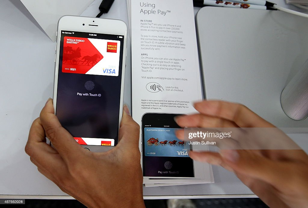 A worker demonstrates Apple Pay inside a mobile kiosk sponsored by Visa and Wells Fargo to demonstrate the new Apple Pay mobile payment system on...