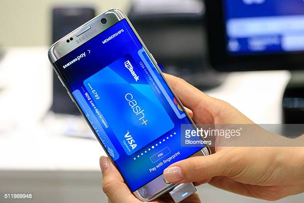 A worker demonstrates fingerprint payment security on the Samsung Electronics Co stand at the Mobile World Congress in this arranged photograph...