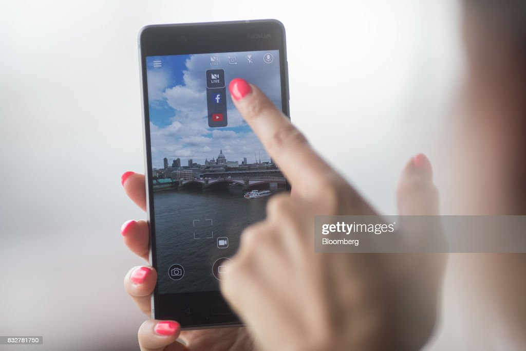 A worker demonstrates live filming capabilities of the Nokia 8 smartphone, designed by HMD Global Oy, ahead of its official unveiling in London, U.K., on Tuesday, Aug. 15, 2017. The phone will feature a dual-sight photo and video function, in which images from the front and rear cameras will be displayed simultaneously on a split screen. Photographer: Simon Dawson/Bloomberg via Getty Images