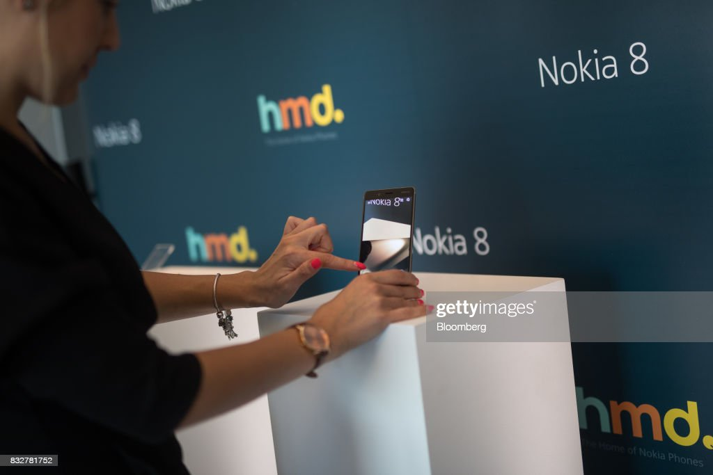 A worker demonstrates the Nokia 8 smartphone, designed by HMD Global Oy, ahead of its official unveiling in London, U.K., on Tuesday, Aug. 15, 2017. The phone will feature a dual-sight photo and video function, in which images from the front and rear cameras will be displayed simultaneously on a split screen. Photographer: Simon Dawson/Bloomberg via Getty Images