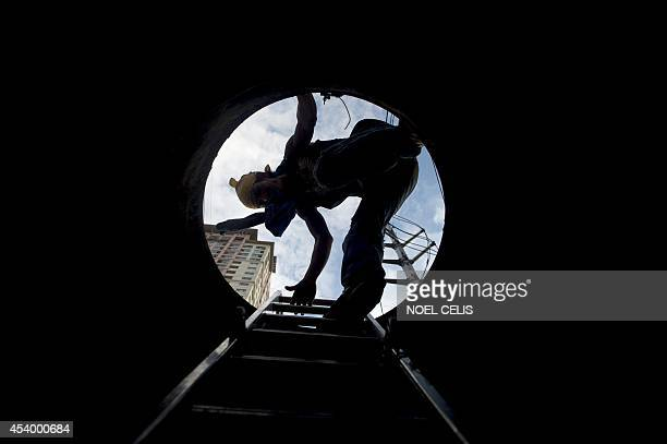A worker descends on a ladder to install fiber optics inside a manhole to improve telephone and internet services in Manila on August 23 2014 The...
