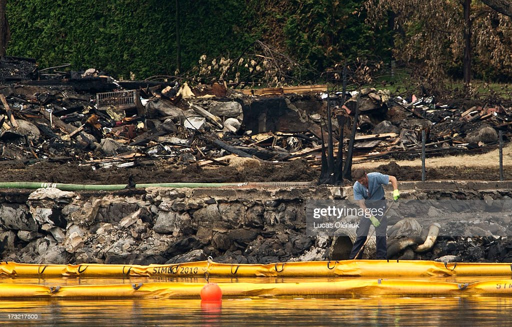 A worker directs crude oil into a pump on the edge of Lac-MÈgantic Tuesday afternoon in front of the explosion zone. Saturday's derailment sent thousands of liters of crude into Lac-MÈgantic and down the ChaudiËre River threatening towns and ecosystems downstream.