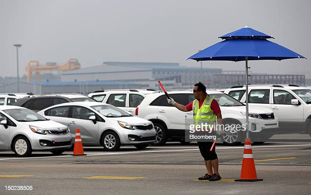 A worker directs Kia Motors Corp vehicles bound for export at the port of Pyeongtaek South Korea on Thursday Aug 9 2012 South Korea's gross domestic...