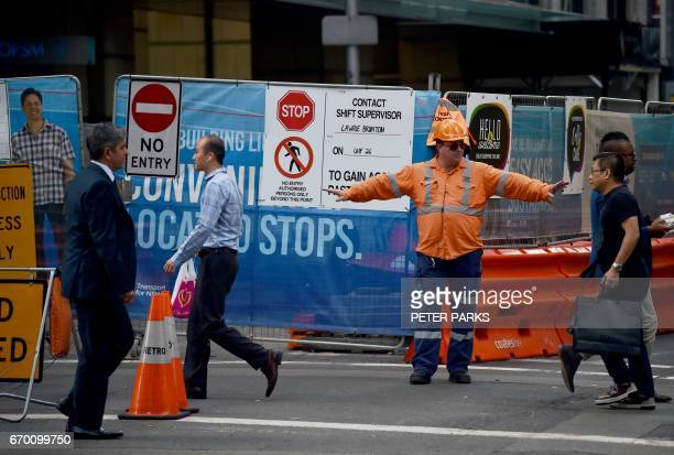 A worker directs pedestrians on a street in the central business district of Sydney on April 19 2017 Australia's controversial decision to scrap a...