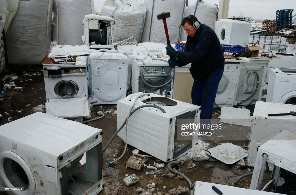 A worker dismantles a washing machine at the Company Induraees factory, specialized in electric and electronic waste recycling, in Osorno, northern Spain, on February 27, 2013. AFP PHOTO / CESAR MANSO