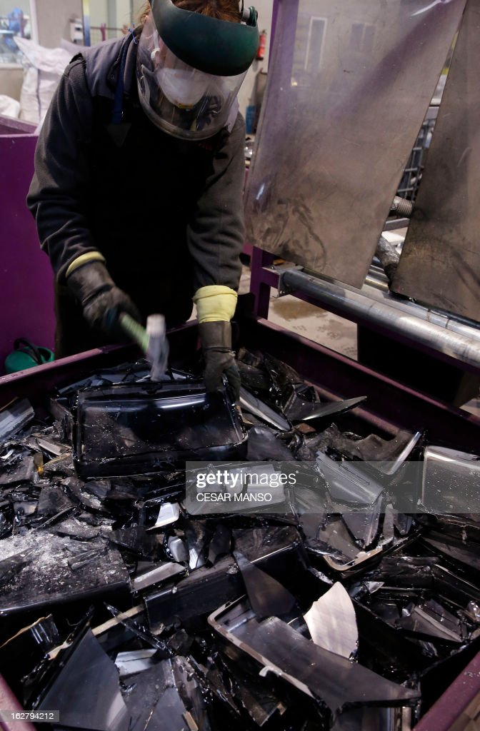 A worker dismantles televisions at the Company Induraees factory, specialized in electric and electronic waste recycling, in Osorno, northern Spain, on February 27, 2013.