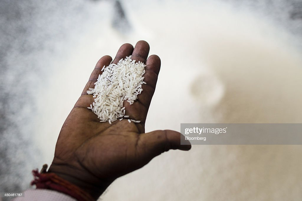 A worker displays a handful of rice for a photograph prior to packaging at the KRK Modern Rice Mill in Kothapeta, Tamil Nadu, India, on Thursday, Nov. 14, 2013. Record onion prices and the soaring cost of rice and coriander are frustrating Reserve Bank of India Governor Raghuram Rajans battle to curb inflation while supporting growth in Asias third-largest economy. Photographer: Prashanth Vishwanathan/Bloomberg via Getty Images