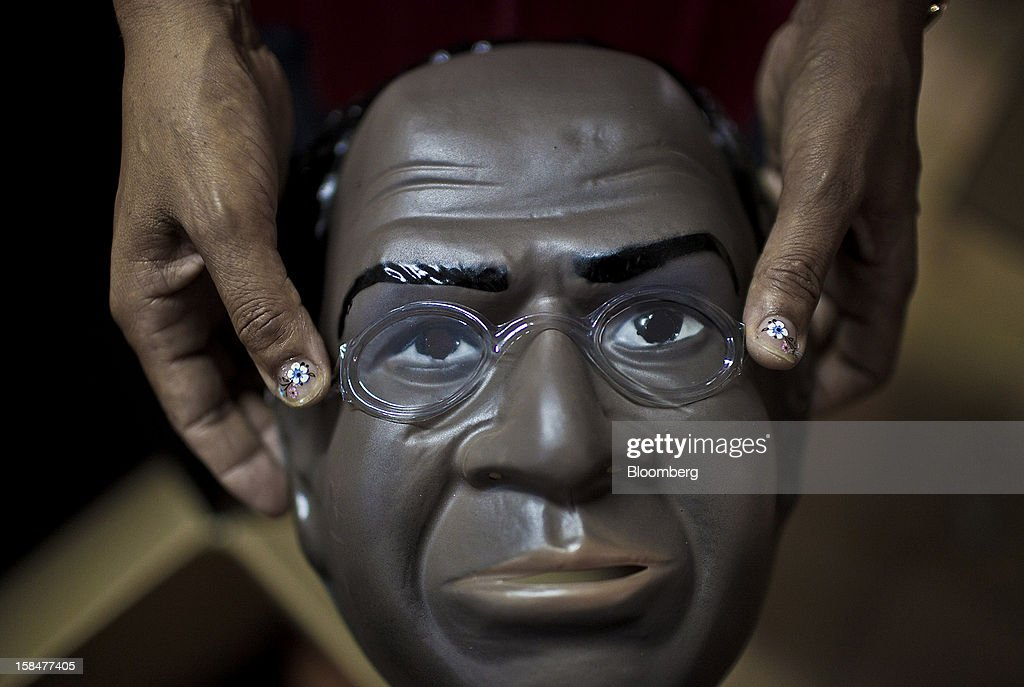A worker displays a Supreme Court Chief Justice Joaquim Barbosa Carnival mask before it is packed for shipment at the Mascaras Condal factory in Sao Goncalo, Brazil, on Monday, Dec. 17, 2012. In a uniquely Brazilian measure of star status, Barbosa masks will be among the most popular during the Carnival celebration in February, according to Rio de Janeiro's O Globo newspaper. Photographer: Dado Galdieri/Bloomberg via Getty Images