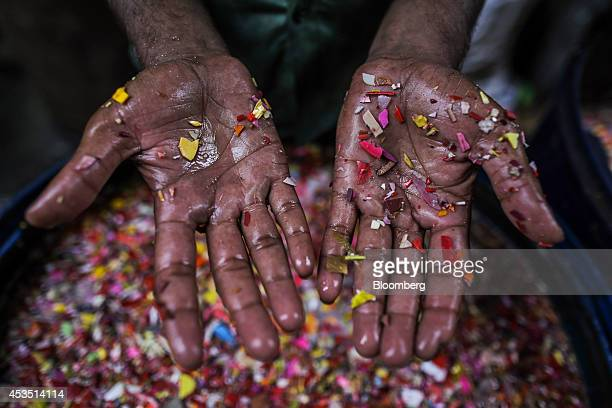 A worker displays his hands for a photograph as he washes shredded plastic waste for recycling in the Dharavi slum area of Mumbai India on Monday Aug...